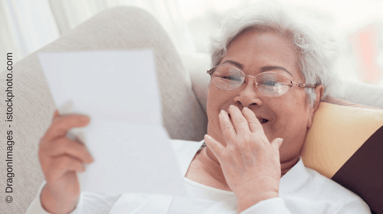 Ältere Frau liest Newsletter per Briefpost
